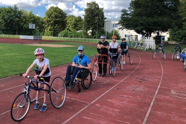 Menschen mit Behinderung mit RaceRunnern auf dem Sportplatz