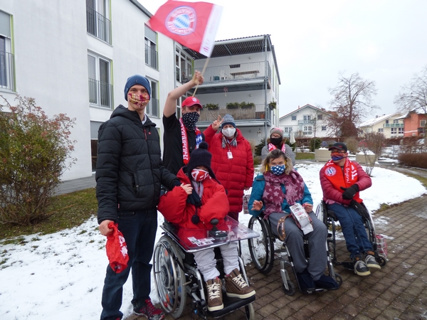 Bewohner*innen der Priener Wohnanlage mit FC Bayern Fanartikeln